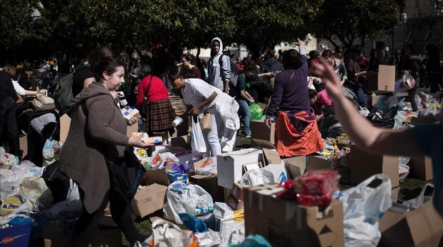 Un grupo de voluntarios reune las bolsas y cajas que han traído vecinos de Atenas para los refugiados.