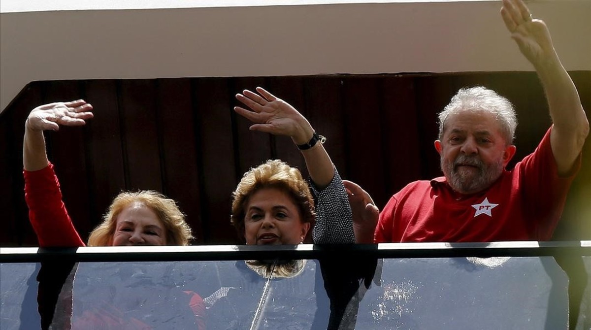 Lula (derecha), Rousseff y la esposa del expresidente, Marisa, saludan desde una ventana de la casa de la parella, en Sao Bernardo do Camopo (Brasil), el 5 de marzo.
