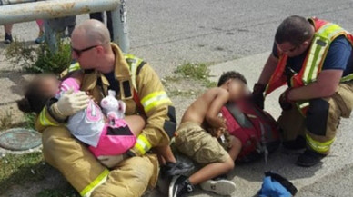 Dos bomberos consuelan a dos niños y la imagen da la vuelta al mundo
