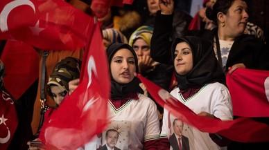 Dos mujeres con pañuelo y banderas turcas, en un mitin del partido gubernamental a favor del 'sí' en el próximo referéndum constitucional, en Ankara, el 25 de febrero.