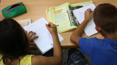 Dos ni�os de primaria haciendo deberes en su casa, despu�s del colegio.