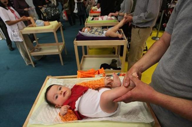 Varios padres, con sus hijos, en una jornada de la feria Mamás-Bebés, en Cornellà.