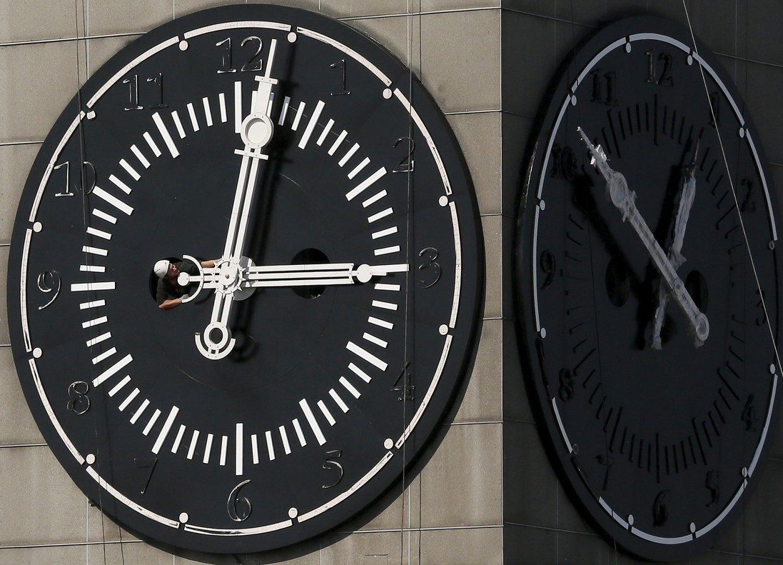 Worker adjusts hands on clock face of city administration building during clocks restoration in Krasnoyarsk