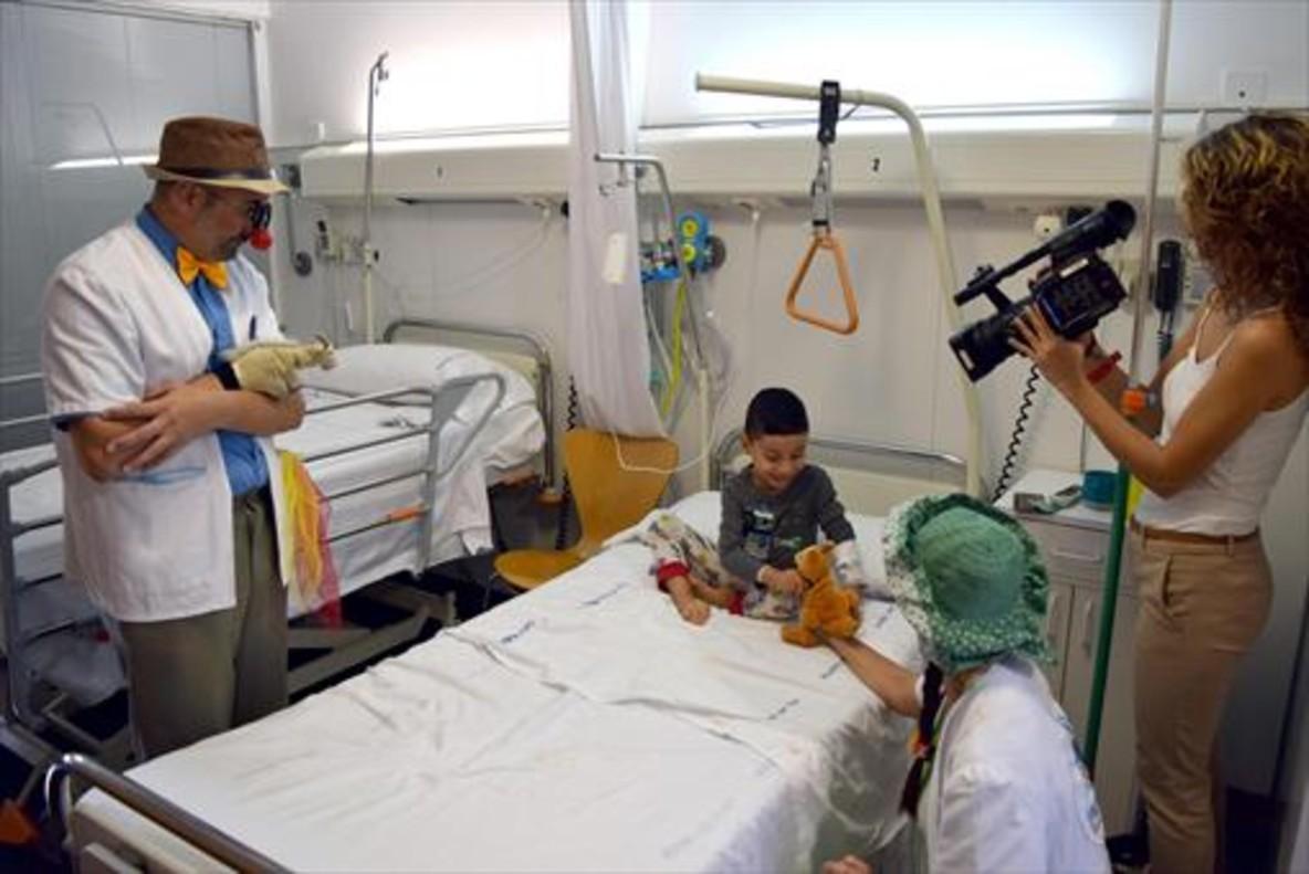 EL RECORRIDO<br/><br/>1. Mireia Rom graba la visita de dos Pallapupas a un niño ingresado en el Hospital del Mar.<br/><br/>2. Portada del libro para ilustrar que se repartirá en plantas de pediatría en el marco de la campaña Un gomet vermell.<br/>