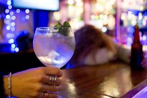 Una mujer sosteniendo una bebida alcohólica en un bar.