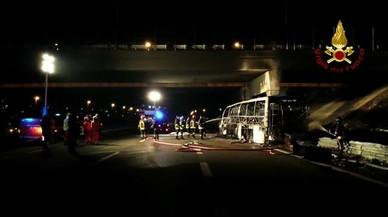 El atobús calcinado, bajo un puente de la A-4 italiana.