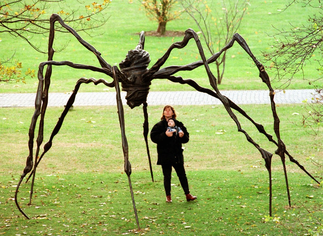 "A mother with her baby examines the sculpture ""Spider"" by French artist Louise Bourgois at Cologne's ""Sculpture Park Exhibition"" Monday November 10, 1997. The 3.5 meters x 5 meters bronze sculpture is one of 30 sculptures of international artists shown in this exhibition. (AP Photo/Roland Weihrauch)"