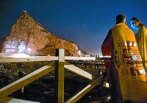 Una pareja mira desde la Línea de la Concepción la proyección de la imagen de Isabel II en el Peñón, el martes.