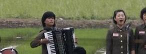 Un grupo de música toca en los campos de la isla de Hwanggumpyong, cerca de la frontera de Corea del Norte.