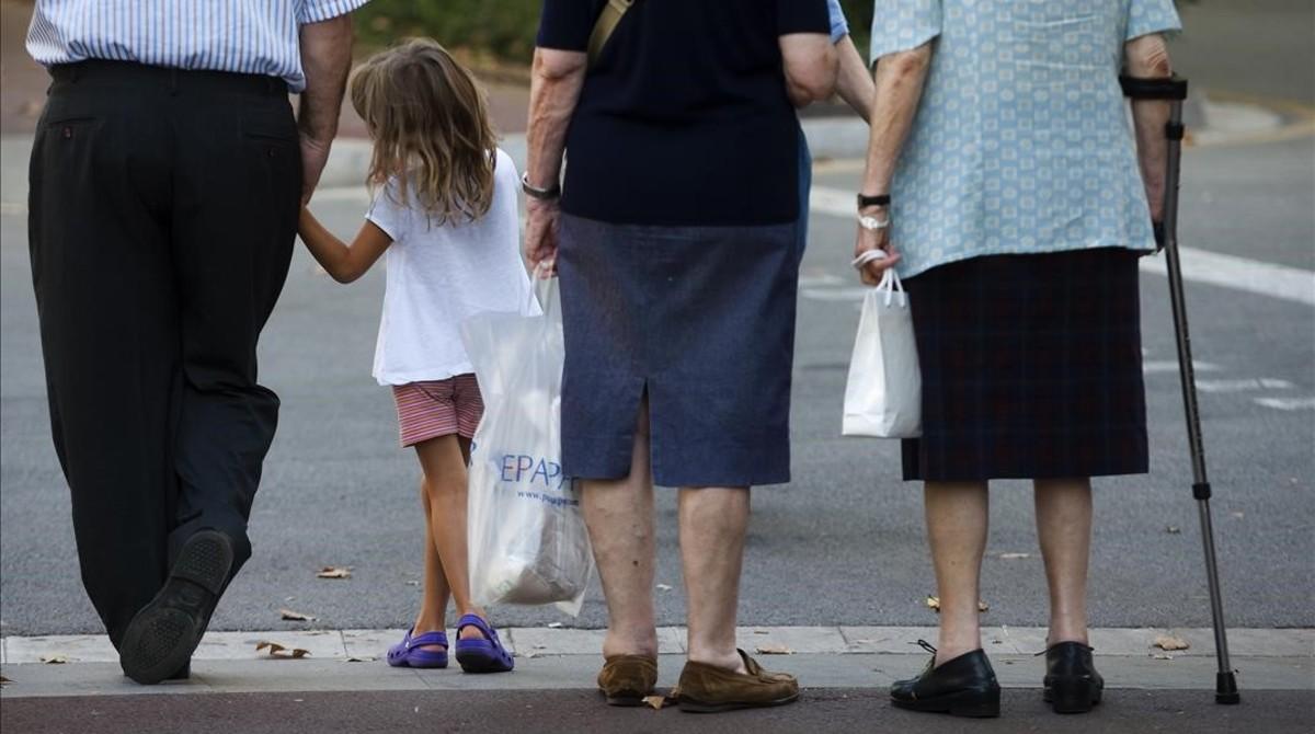 Tres generaciones de ciudadanos a la espera de cruzar una acera.