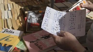 Felicidad sostiene la lista con los títulos que le faltan de varias colecciones de novela romántica, en la tienda de libros de Joan Mateu.
