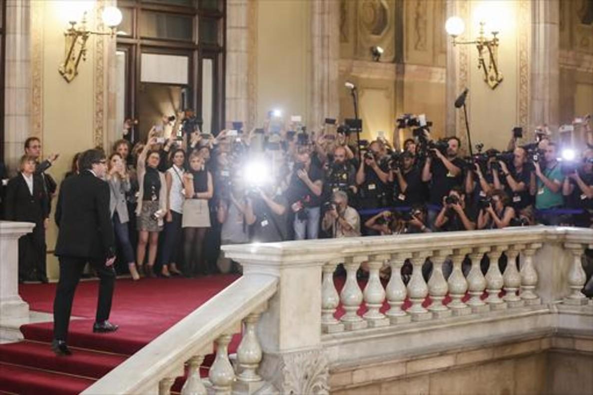 Puigdemont llega al Parlament entre una nube de fotógrafos, el martes, antes de su comparecencia en el pleno.