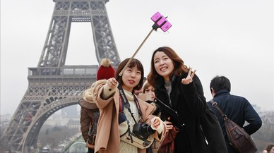 Un grupo de turistas orientales ante la Torre Eiffel.