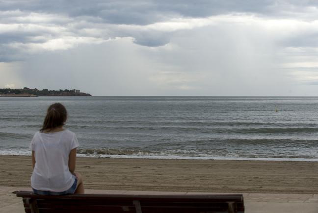 Una mujer mira el cielo, que amenaza lluvia.