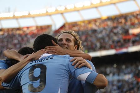 Diego Forlán celebra con Luis Suárez (de espaldas) la victoria de Uruguay, este domingo, en Buenos Aires.