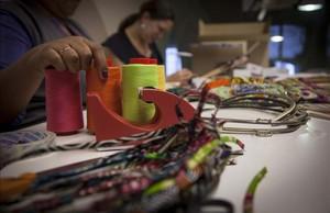 Unes dones treballen al taller dartesania.