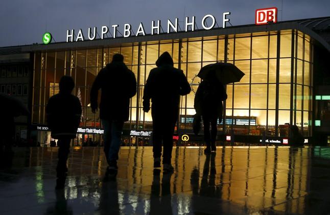 Un grupo de gente camina frente a la estación de tren de Colonia