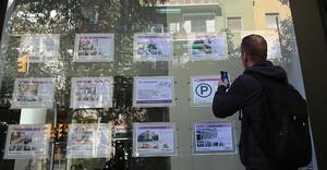 Hombre busca un piso de alquiler en una inmobiliaria de Barcelona.