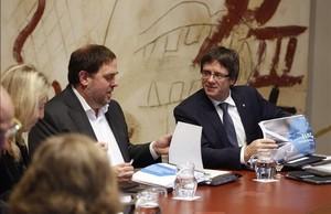El vicepresidente del Govern, Oriol Junqueras, y el president, Carles Puigdemont, con el proyecto de ley de los presupuestos de la Generalitat para el 2017 en la reunión del Consell Executiu, este martes.