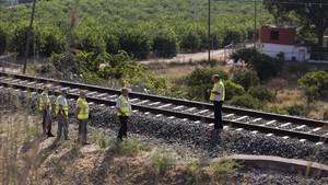 Un guardia civil inspecciona la zona acotada de la via ferrea donde un maquinista ha encontrado el cuerpo de Lucia Vivar Hidalgo