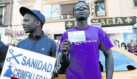 Dos inmigrantes se manifiestan contra el cobro de la tarjeta sanitaria en Madrid..