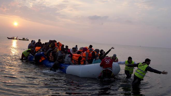 Varios voluntarios ayudan a un grupo de refugiados a llegar a la costa, en la isla griega de Lesbos, el pasado marzo.