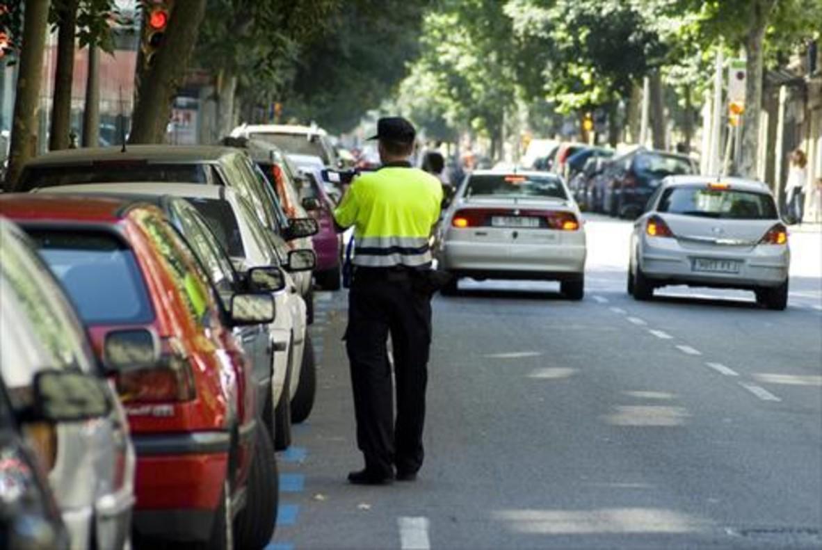 Un empleado de BSM impone una sanción a un vehículo aparcado en la zona azul de la calle de Girona.