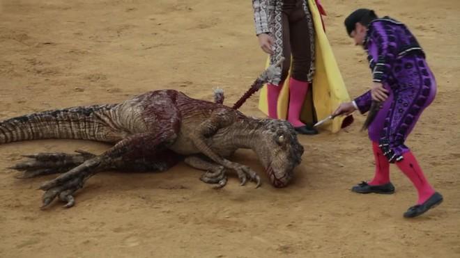 Un velociraptor es toreado, banderilleado y estoqueado en una plaza por un matador y su cuadrilla.