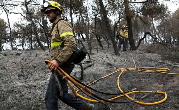 Los equipos de extinción apagan las brasas tras el paso del fuego en Òdena (Anoia).
