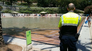 Un agente de la Guardia Urbana, junto al lago del parque de la Creueta del Coll.