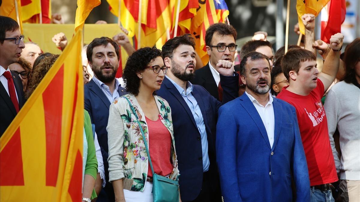 """Miembros d'ERC cantando """"Els Segadors"""" ycon Rufián con el puño en alto."""