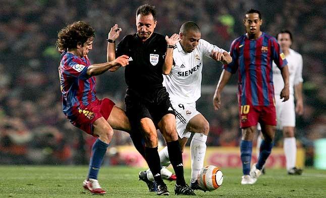 Ronaldo, de blanco. El �rbitro Medina Cantalejo obstaculiza a Puyol en su marcaje a Ronaldo en el partido del 1 de abril del 2006.