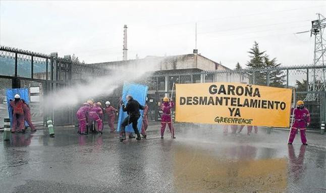 Miembros de Greenpeace reciben manguerazos para evitar su acceso a la central, ayer en Garoña.<BR/>