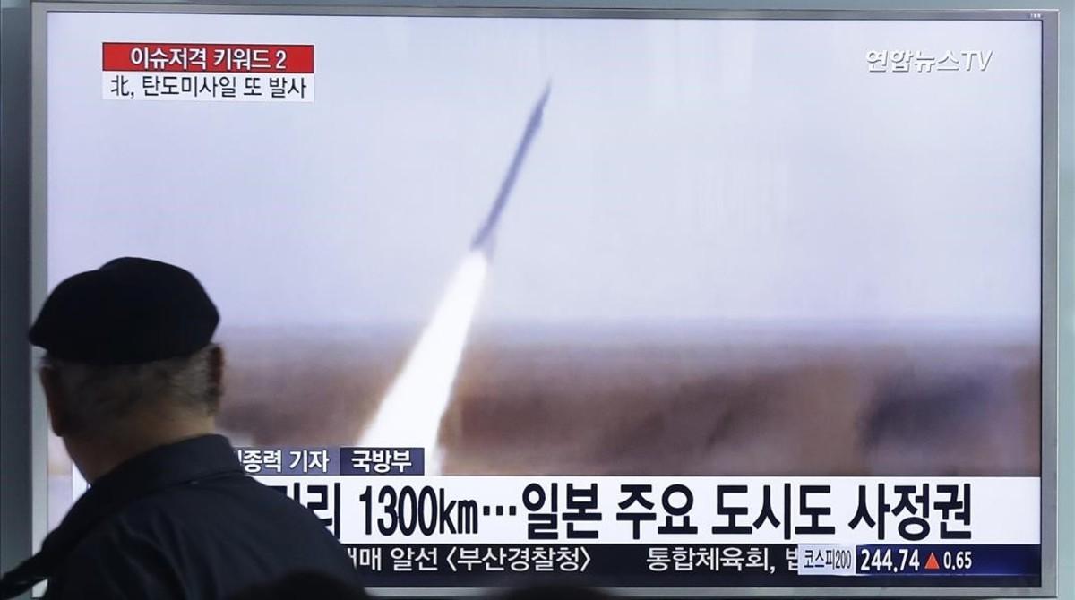 Un hombre sigue por televisión el lanzamiento del misil.