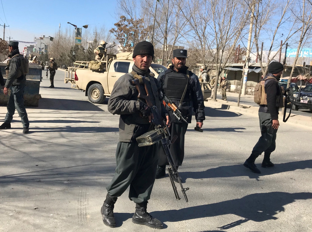 Afghan policemen stand guard at the site of a blast in Kabul