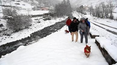 Unos turistas caminan por la nieve en Espot, este sábado.