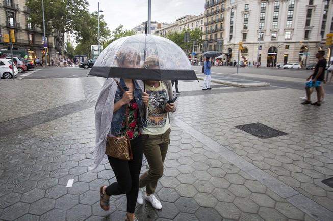 Dos mujeres se protegen de la lluvia en Barcelona.