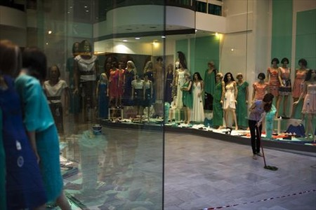 Una dependienta limpia la entrada de una tienda de ropa ubicada en una c�ntrica calle de Atenas.