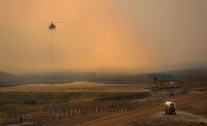 Un helicóptero recoge agua para apagar un gran incendio en Wyoming.