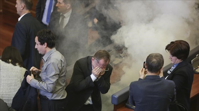 Un diputado se tapa los ojos tras lanzar una bomba de gases lacrimógenos, este viernes, en Kosovo.