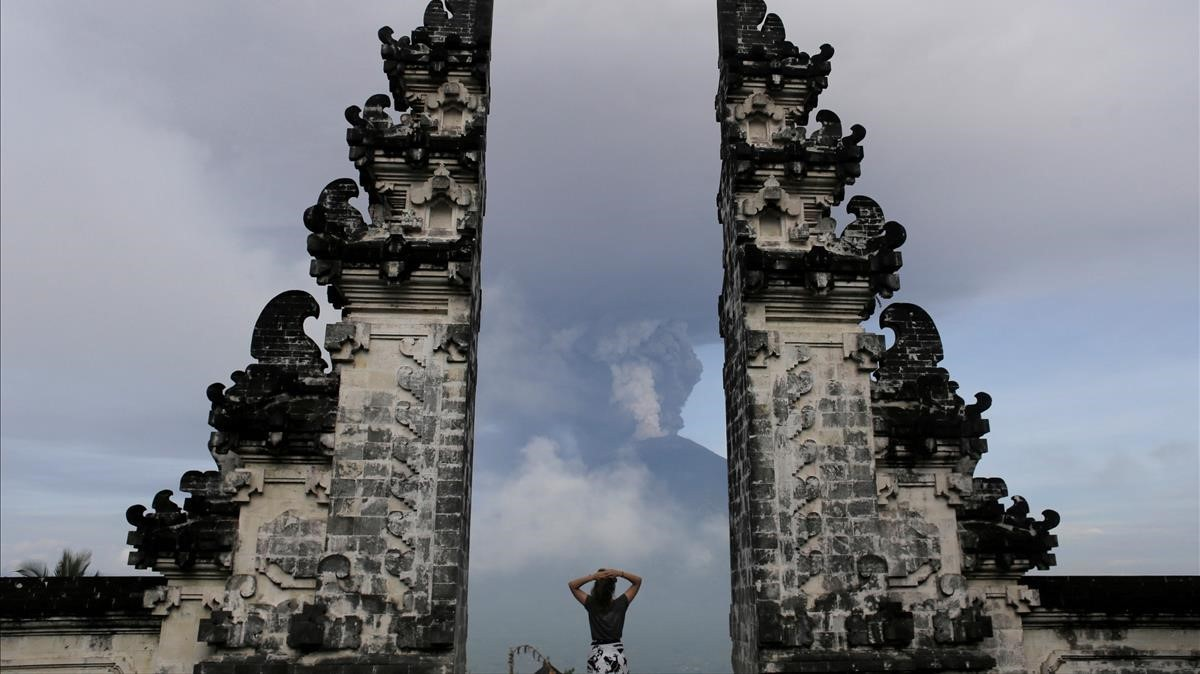 abertran41098972 a tourist watches as mount agung volcano erupts at lempuyang171127130623