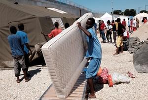 Un eritreo carga con un colchón en un campo de refugiados en Roma.