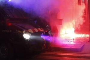 Varios mossos intentan sofocar uno de los incendios provocados por los radicales, anoche en Gràcia.