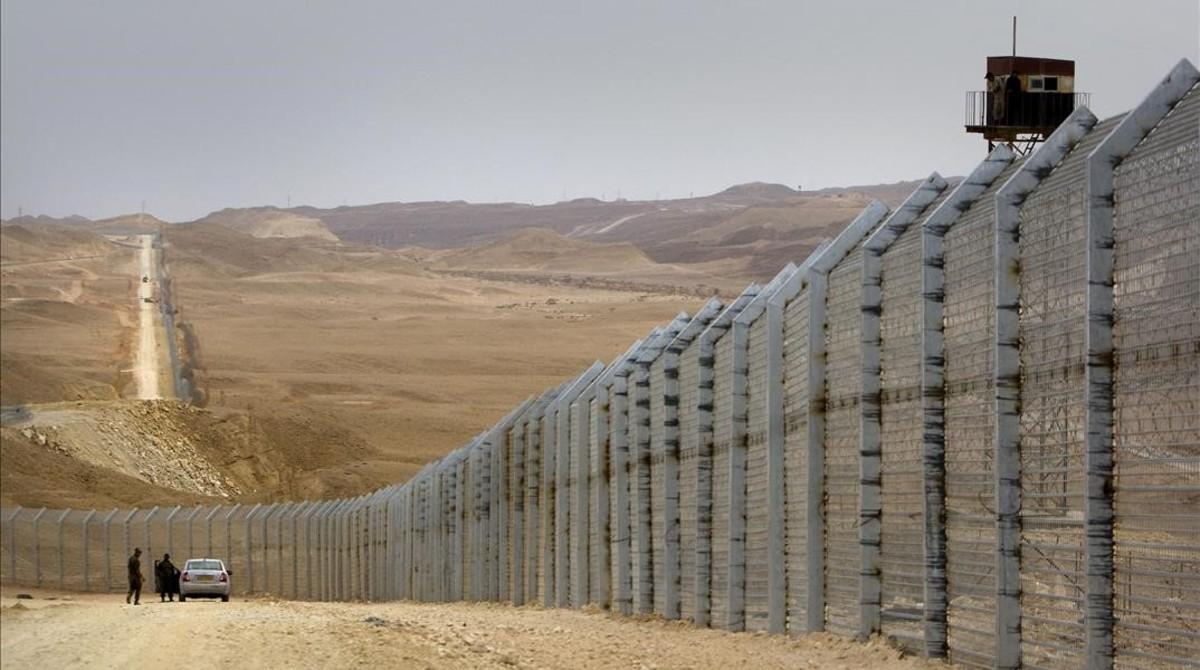 Guardias egipcios (derecha) observan desde una torre de vigilancia cómo sus homólogos israelís supervisan la construcción de una valla fronteriza entre Israel y Egipto, cerca de Eliat, el 15 de febrero del 2012.