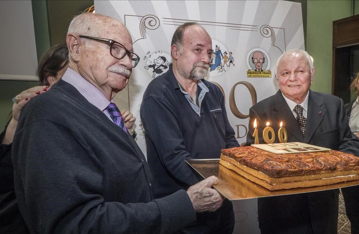 El histórico dibujante de TBO Josep Maria Blanco, Antoni Guiral, autor de 100 años de TBO, y Lluís Giralt, que ha colaborado en el libro, a punto de soplar las velas del aniversario de la mítica revista de cómic.