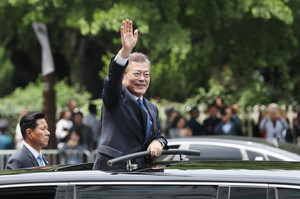 South Korean President Moon Jae-in waves as he leaves the National Cemetery after inaugural ceremony in Seoul