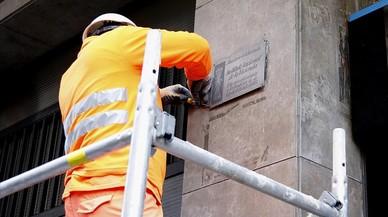 Un operario retira una placa franquista de un edificio de la calle de Còrsega, este lunes.