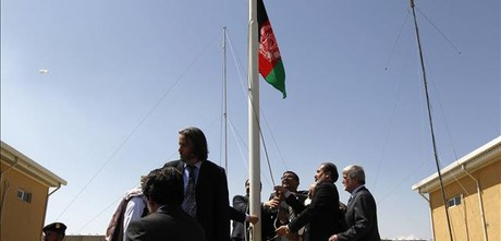 Oficiales afganos hizan la bandera de su pas en Bagram.