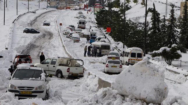 Vehículos atrapados en la nieve en Jerusalém. La ciudad se ha paralizado por una fuerte tormenta de nieve.
