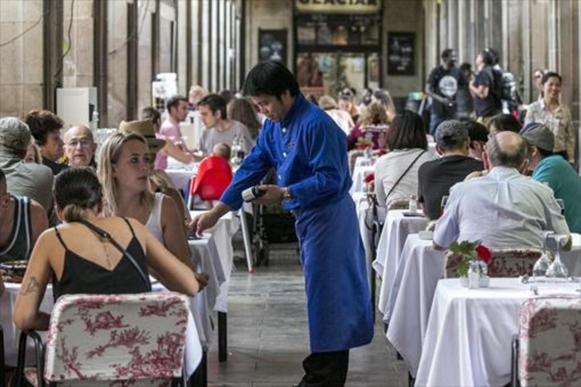 Un camarero sirve en una terraza de la plaza Reial de Barcelona, ayer.